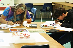 2 youth/students drawing cupcakes